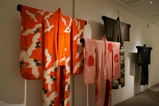 Japanese kimono. The two brightly coloured kimono in front are for unmarried women, as shown through the longer sleeves. The two black kimono in back are for married women, since they have shorter sleeves. Layers of Influence exhibtion, MOA at UBC Photo cred: Lauren Chancellor
