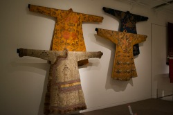 Tibetan robes from ~1650, part of the Yapshi-Yuthok Kalon Tashi Dhondup collection. Families with a Dalai Lama born into the family are given the designate Yapshi. On the bottom left is a Khakhazouk (~1850), worn by government officials on special occasions. Layers of Influence exhibtion, MOA at UBC Photo cred: Lauren Chancellor